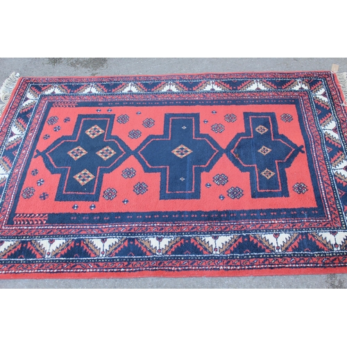 34 - Turkish rug with triple medallion and multiple borders on a red ground, approximately 68ins x 45ins