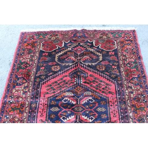 7 - Zanjan rug with a medallion and all-over stylised design on a dark ground with borders, 2.06m x 1.4m