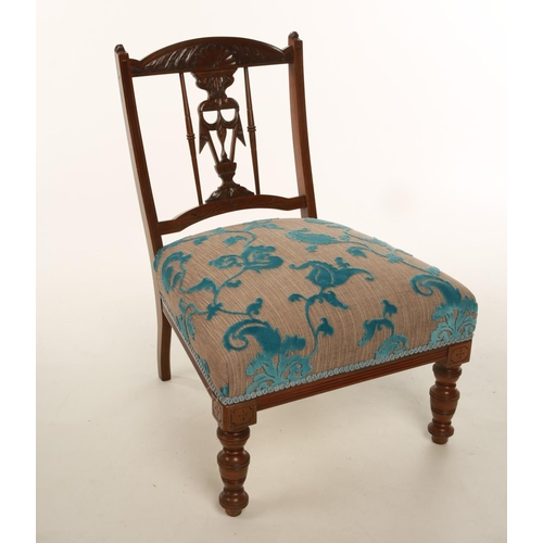 19 - A late Victorian / Edwardian walnut framed low seated nursing chair with recently upholstered seat