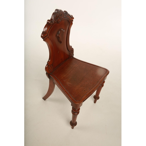 27 - A Georgian style Golden oak carved hall chair; the back carved with Arabesque scrolls and pokerwork ...