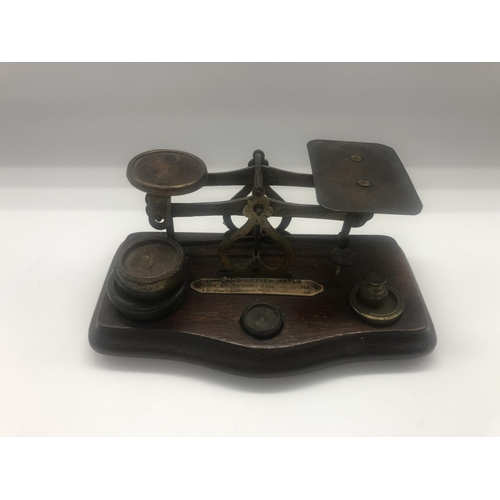 40 - A set of mid 20th century mahogany and brass postage scales; complete with weights; raised on plinth...