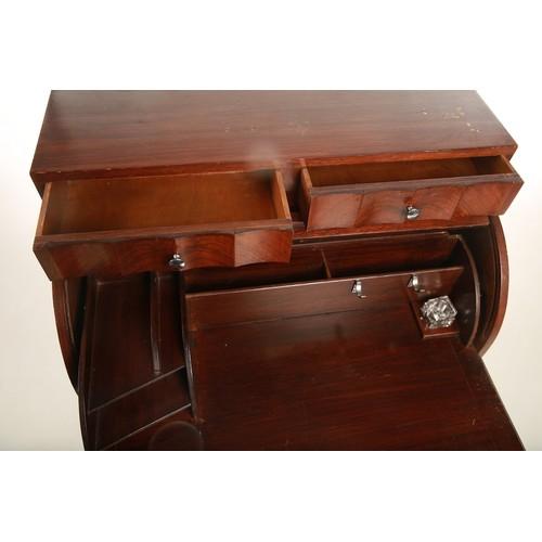 57 - An Art Deco mahogany roll top writing bureau raised above a pair of inverted linen fold doors openin...