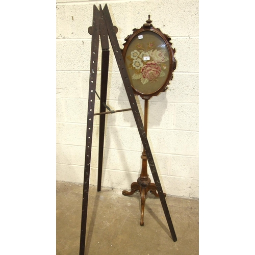 59 - A Victorian walnut pole screen with oval needlework panel, 37 x 47cm, on tripod support 150cm high a...