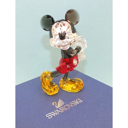 A Swarovski coloured crystal Disney figure of Mickey Mouse, standing sideways with both arms towards the left, 10.5cm high, (boxed, with original packaging, as new).
