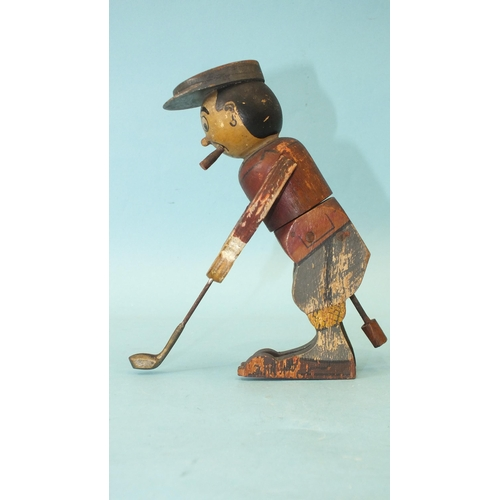 A wooden toy in the form of a golfer teeing off, the figure twisting from the waist, constructed from painted wood, with metal club, 16.5cm high.