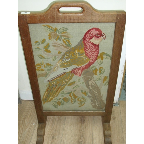 189 - Robert Thompson 'Mouseman' oak fire screen with inset wool work embroidered panel of a parakeet (47c...