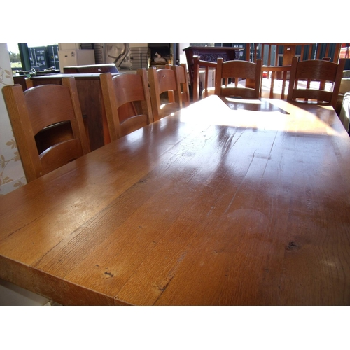 437 - A large heavy oak dining table with X shaped under tier and stretcher (length 240cm) and a set of si...