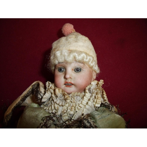 9 - Scarce and unusual French porcelain hand spinning doll, the porcelain head with blue glass eyes and ...