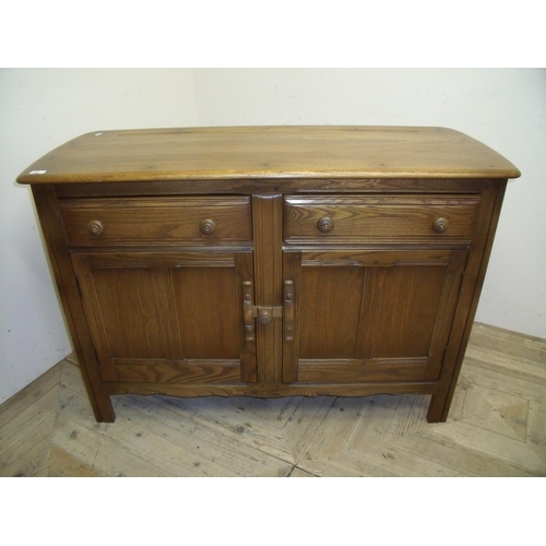 334 - Ercol medium coloured elm 4ft sideboard with two drawers above two panelled cupboard doors...