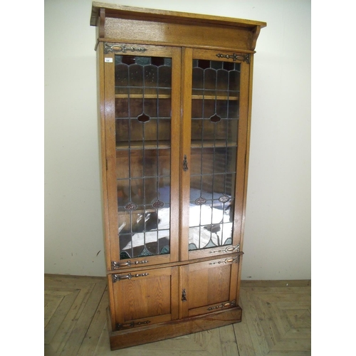 335 - Early 20th C golden oak cabinet with two upper lead glazed cupboard doors above two panelled doors (...