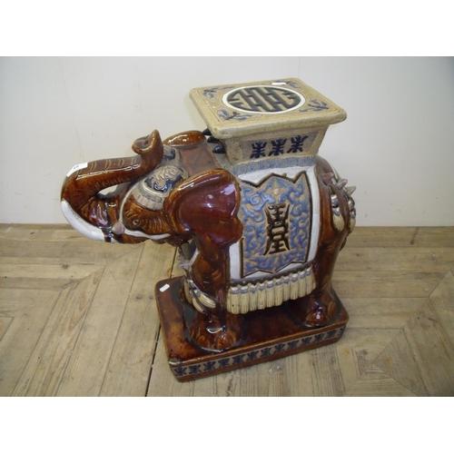 32 - A mottled glazed ceramic elephant stool  (56 cm high)...