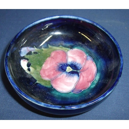 22 - signed William Moorcroft shallow bowl on raised base with central pansy type flower (11.5cm x 4cm)...