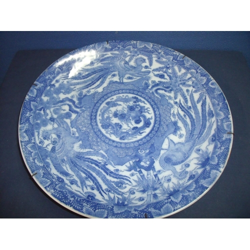 12 - 19th/20thC oriental blue and white charger with central circular dragon pattern within a border of b...