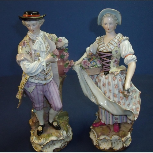 10b - Pair of Meissen porcelain figures depicting a continental couple carrying baskets of flowers with bl...