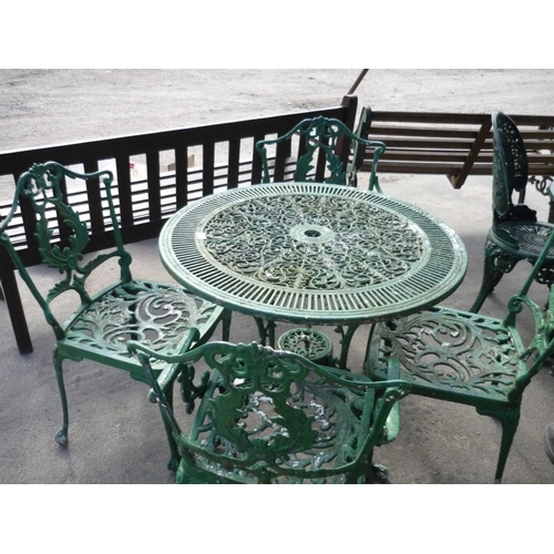 23 - Table and four chairs in wrought iron...
