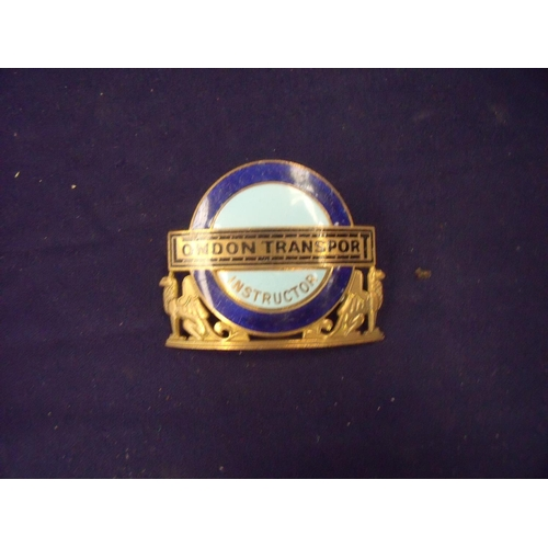 84 - Gilt metal and enamel London Transport Instructors cap badge...