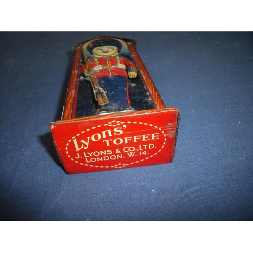 188 - Vintage tin plate Lyons Toffee Guardsman money box Pat No 3738 by D.R.G.M (23cm high)...