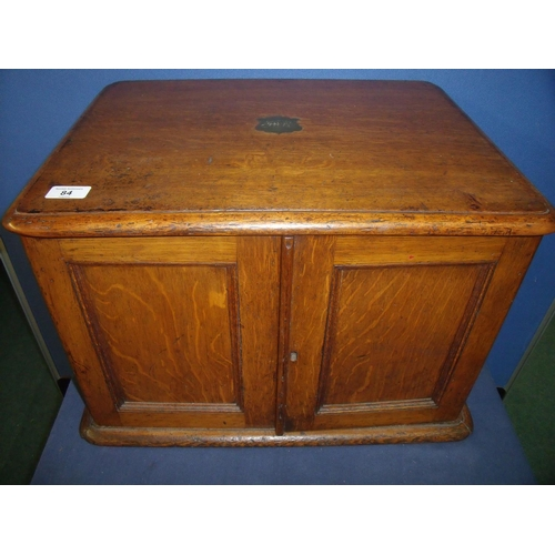 84 - Edwardian oak table box with inset brass carry handles, enclosed by two panelled cupboard doors reve...