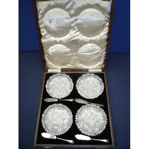 16 - Cased set of four quality cut glass butter dishes with four Birmingham silver hallmarked butter kniv...