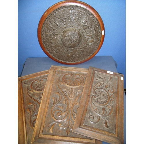 38 - Three 19/20th C carved oak panels and an embossed bronze circular type shield depicting various batt...