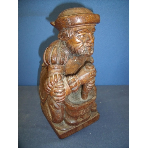 55 - Carved oak figure of a alchemist/apothecarist kneeling at pestle and mortar (32cm high)...
