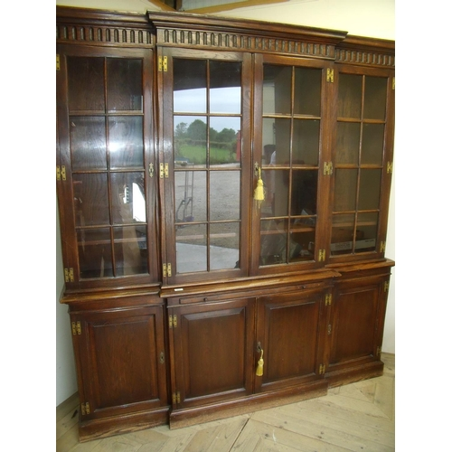 520 - Quality modern oak breakfront bookcase with four glazed doors above central slide and four panelled ...