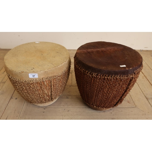 37 - Pair of African style tribal drums finished in animal skin with rope decoration...