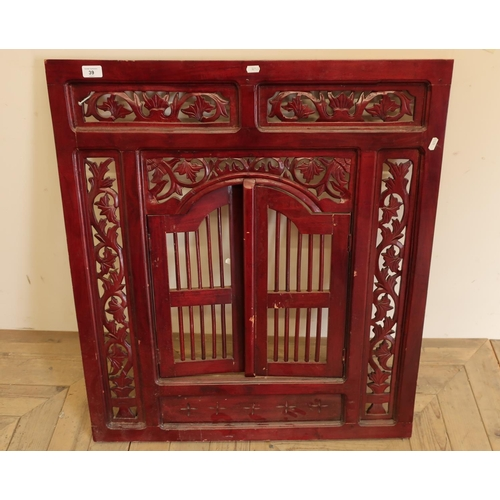 39 - Decorative wooden panel with vine type border and a central opening section of two doors...