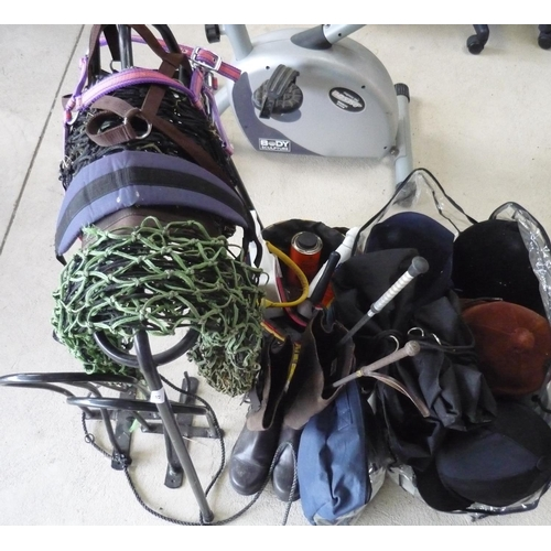 57 - Collection of horse tack including boots (size 5), four riding helmets, bridles, saddle holder, hay ...