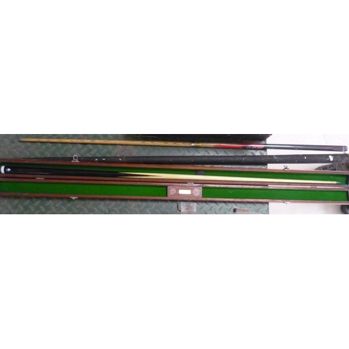 36 - Three snooker cues, one in vintage metal carrying case, one in wooden carrying case...