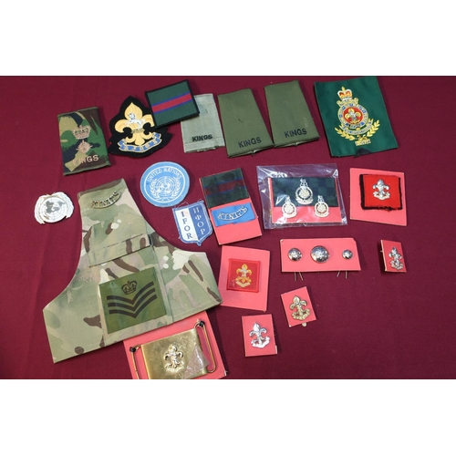 13 - Box containing a quantity of Kings regiment insignia including rank slides, cap badges, shoulder tit...