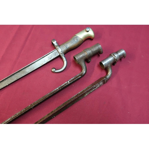 18 - Two 19th C socket triangular form bayonets and a French bayonet, the top strap marked 1880 (3)...
