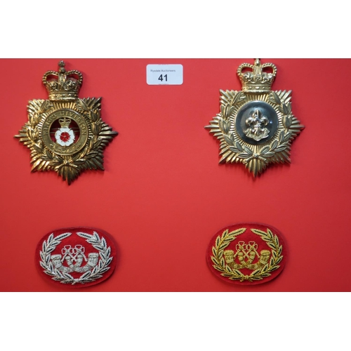 41 - Board mounted with staybright Kings Division Regiment helmet badges and two embroidered bugle badges...