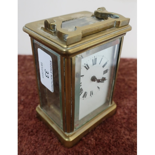 33 - Brass cased French made carriage clock with white enamel dial, complete with key and swing handle (h...
