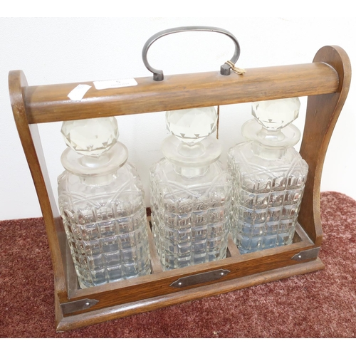 5 - Mid - late 20th C oak three sectional Tantalus, with three glass decanters...