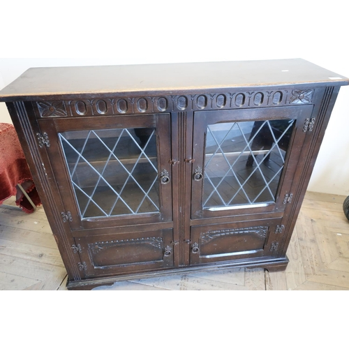 226 - Oak cabinet enclosed by two lead glazed doors above two further cupboard doors (111cm x 33cm x 99cm)...