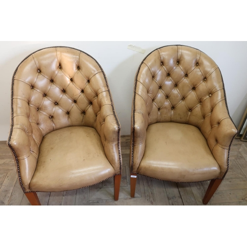 228 - Pair of early - mid 20th C tan leather deep button back armchairs on tapering supports...