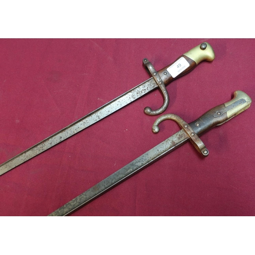 49 - Two 19th C French/Belgium tri-form bayonets, the top straps dated 1878 with brass and wood grips, th...