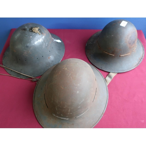267 - Three WWII British steel helmets, two complete with liners, one marked S.M.LD 1941 (3)...