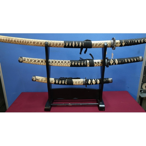 436 - Set of three decorative Japanese style samurai swords with stand...