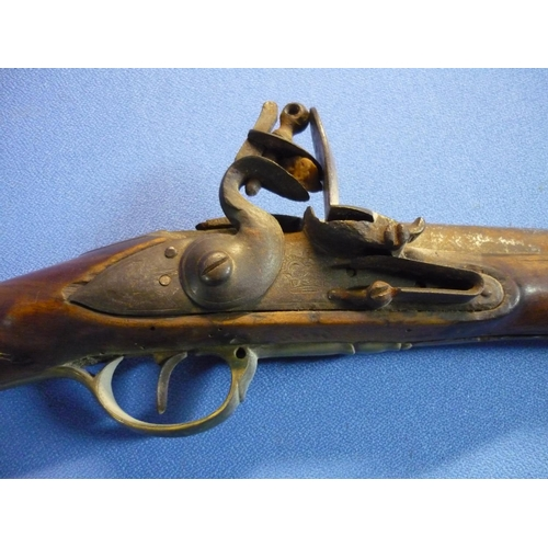 65 - Indian flintlock carbine with 30 1/2 inch barrel with brass mounts and trigger and butt guards, the ...