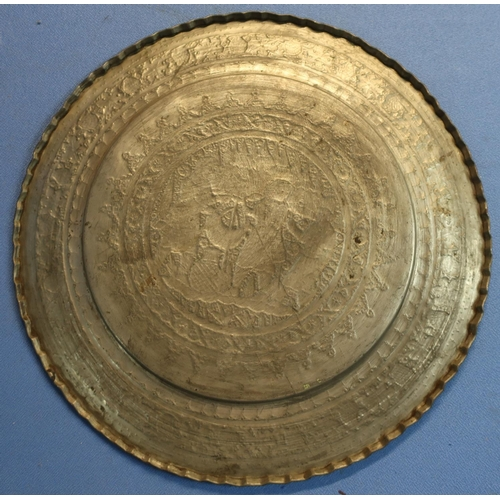 126 - Pewter charger, the centre of the charger depicting native eastern scenes, and two brass chargers (3...