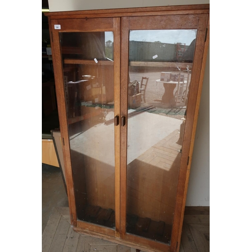 144 - Early to mid 20th C oak gun style cabinet enclosed by two glazed doors with internal shelf and gun r...