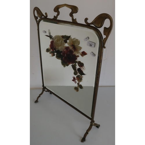 89 - Art Nouveau brass framed fire screen, the bevelled edge mirror panel with painted floral detail...