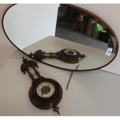 39 - Oval oak framed bevelled edge wall mirror and a carved oak framed wall barometer (2)...