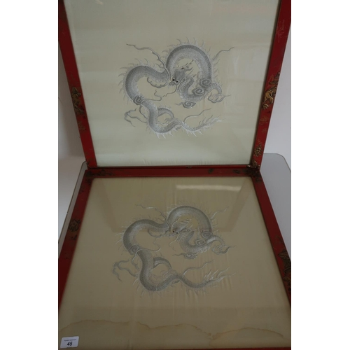 45 - Pair of framed and mounted embroidered Oriental silkwork panels of dragons in red chinoiserie frames...