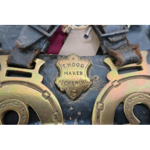 28 - Collection of fifteen Victorian horse brasses on three leather straps, stamped T Hood, Maker - Picke...