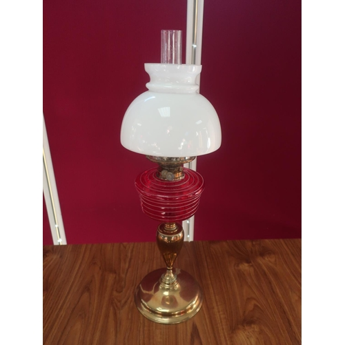 459 - Early 20th C brass oil lamp, with red glass reservoir and clear glass shade, on urn shaped column an...