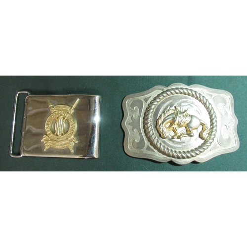 17 - Metal belt buckle with a bucking bronco and a belt buckle with the badge of the Kenyan Prisons Servi...