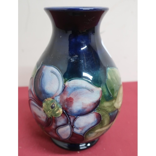 24 - Moorcroft pottery vase, the baluster body decorated with a clematis pattern on a blue ground, facsim...